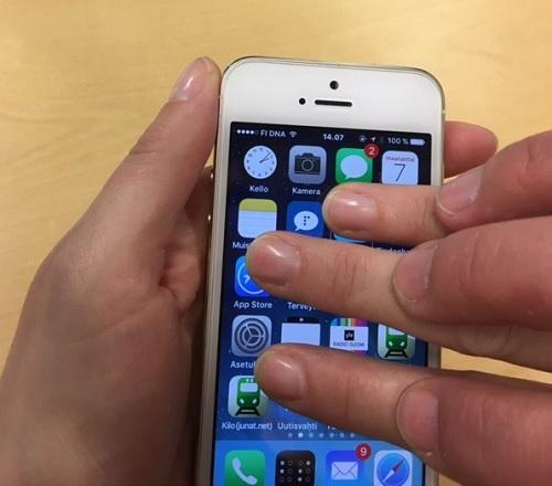 Kosketusnäytöllä tehdään kolmen sormen vaakapyyhkäisyä. Ohjaajan sormet näkyvät oppilaan sormien päällä.