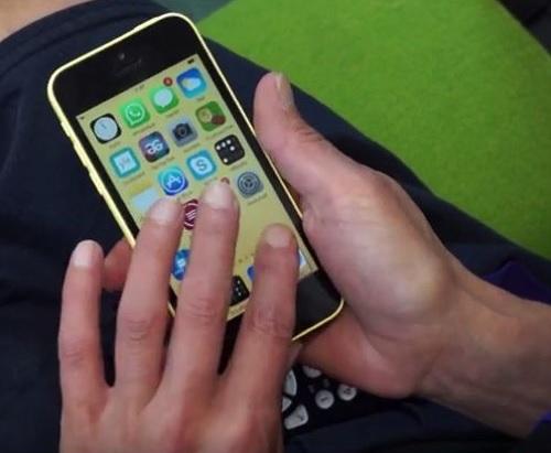 Älypuhelin, jota käsi pitelee ja jonka kosketusnäyttöä toinen käsi on koskettamassa.