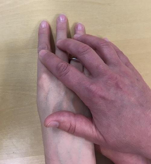 Ohjaajan käsi on oppilaan kolmen sormen ja kämmenselän päällä.